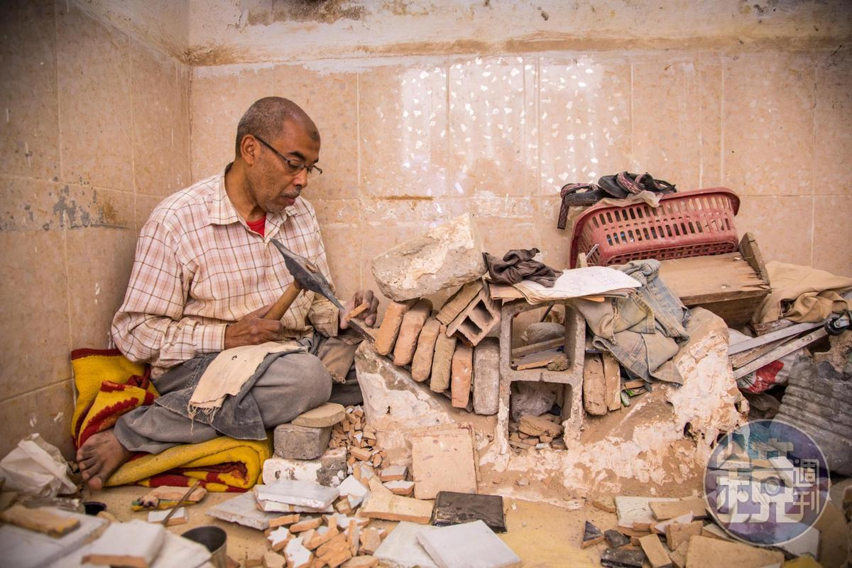 街道旁的屋內,一個老頭兒正在鑿磁磚雕花。