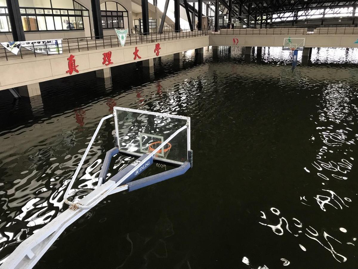 網友po出台南真理大學麻豆校區大禮堂籃球場成了大水池,可見這幾天驚人的雨量。(翻攝自網路)