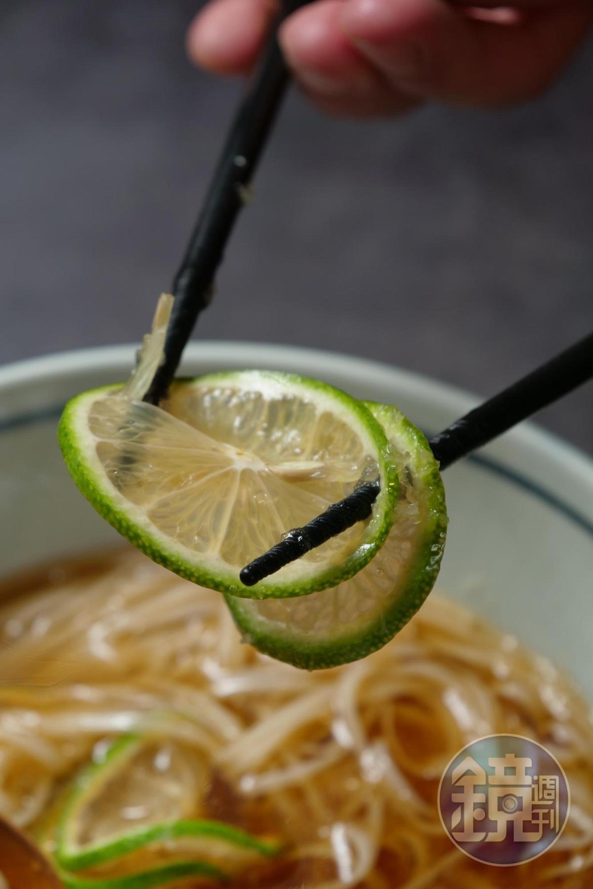 用筷子將檸檬片扭結擠汁。