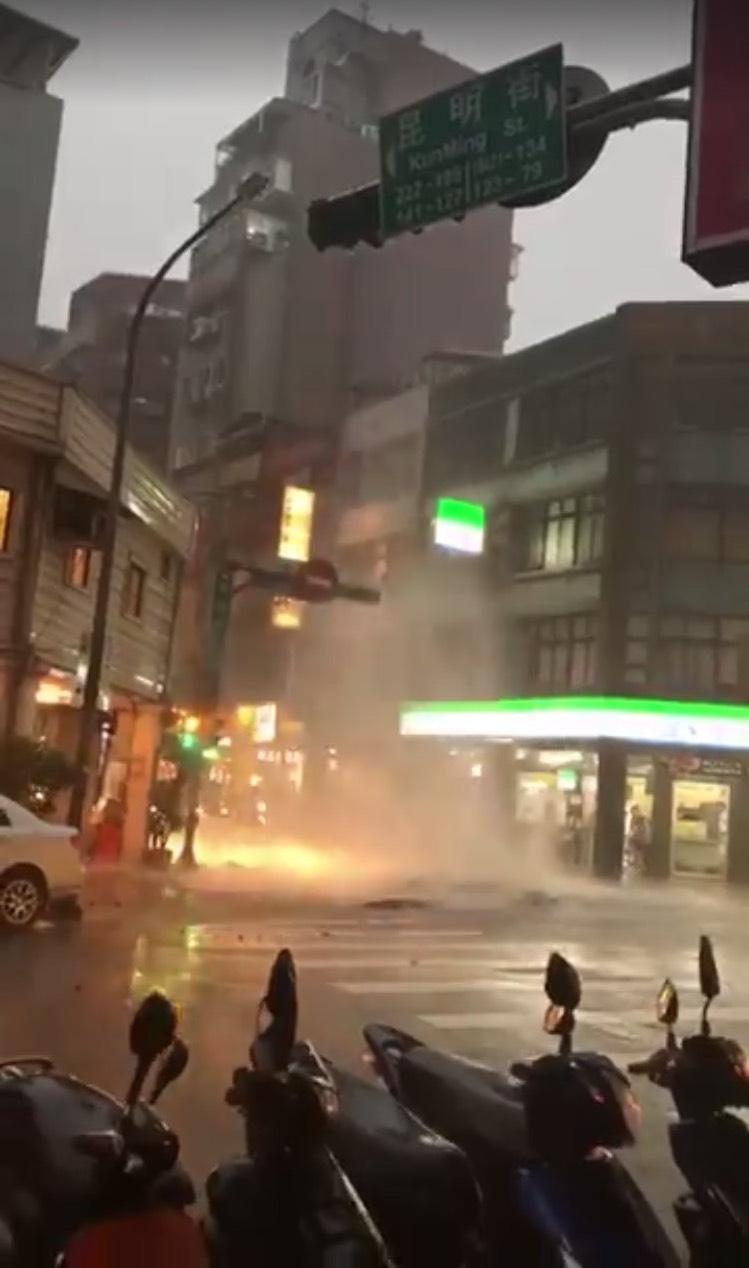 北市萬華區昆明街人孔蓋遇大水噴發。(翻攝畫面)