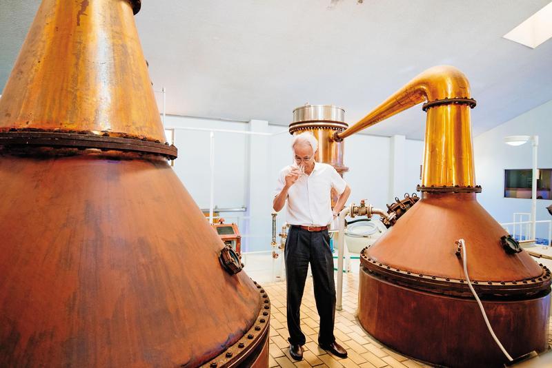 社長平石幹郎站在一對紅銅蒸餾器旁,嗅聞剛蒸餾出來的新酒。左為一次蒸餾器,5,000公升;右為二次蒸餾器,3,000公升。