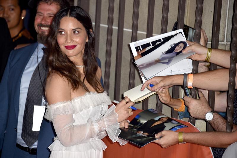 在多倫多影展紅毯替粉絲簽名的奧莉薇亞穆恩,踢爆《終極戰士:掠奪者》雇用性侵前科演員,卻帶來意想不到的後果。(東方IC)