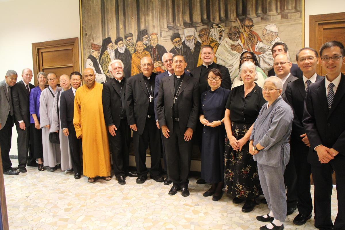 跨宗教團隊在宗座宗教交談委員會一幅代表各宗教的油畫前,與米格爾·阿尤索主教(Bishop Miguel Ayuso)合影。(慈濟基金會提供)