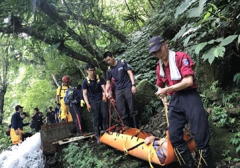 當地地形陡峭,搜救人員小心翼翼地運送他們下山。(消防局提供)