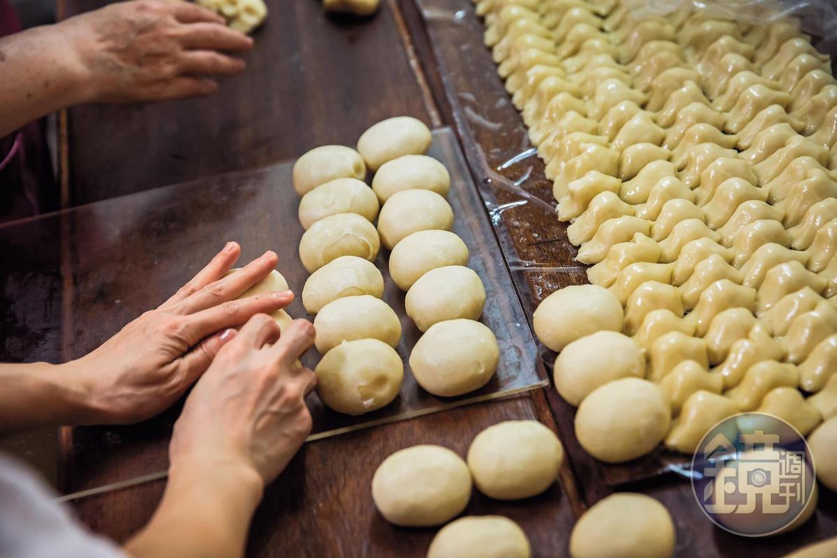 餅皮包餡後,還得逐一經過手工塑形,才能進入下一道工序。