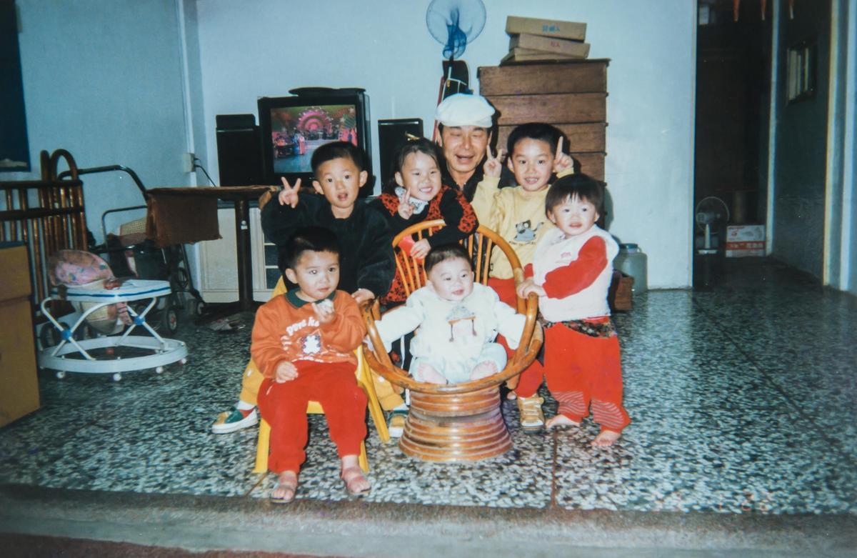 蘇義源與孫子們的全家福,後面疊高的木箱正是用來裝牛舌餅。(明豐珍兔仔寮牛舌餅提供)