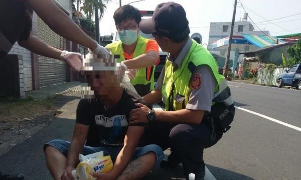廖姓男子血淋淋持刀街頭暴走嚇壞路人,警方與消防人員緊急處理。(警方提供)