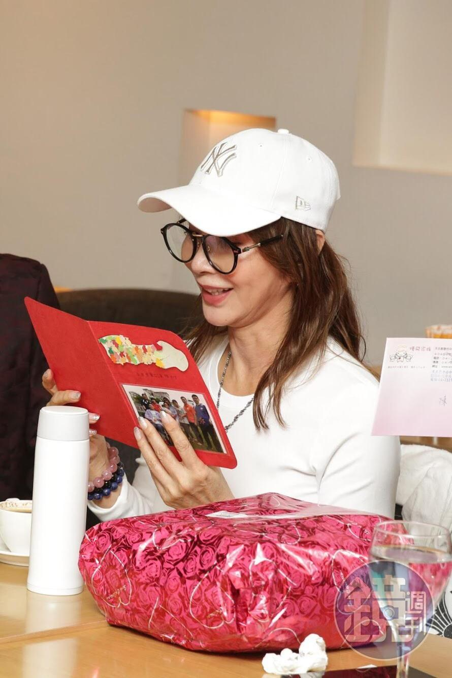 陳美鳳看著受幫助的孩子寫給她的卡片,表情滿是感動。