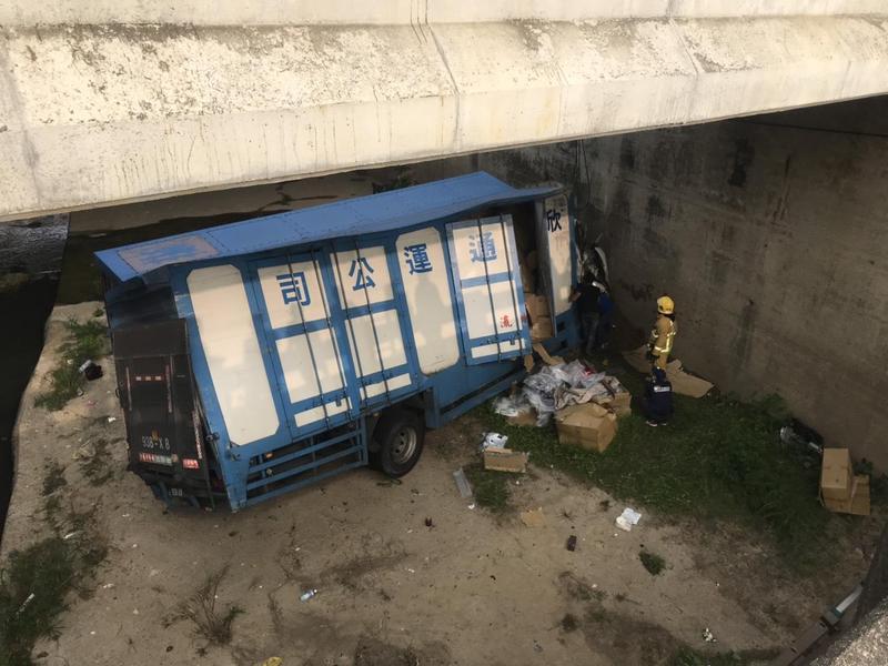 物流公司貨運車翻落約2至3層樓深的大排下,車頭嚴重凹陷變形,車體也扭曲,貨物散落一地。(警方提供)
