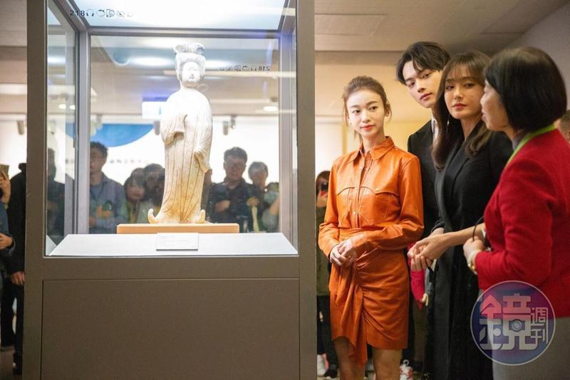 三人專心觀看唐代灰陶加彩仕女俑並聽導覽人員解說。