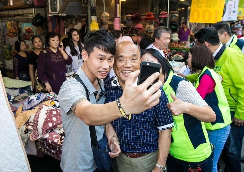 民進黨新北市長候選人蘇貞昌今到板橋區市場掃街拜票,熱情民眾與他自拍留念。(蘇貞昌辦公室提供)