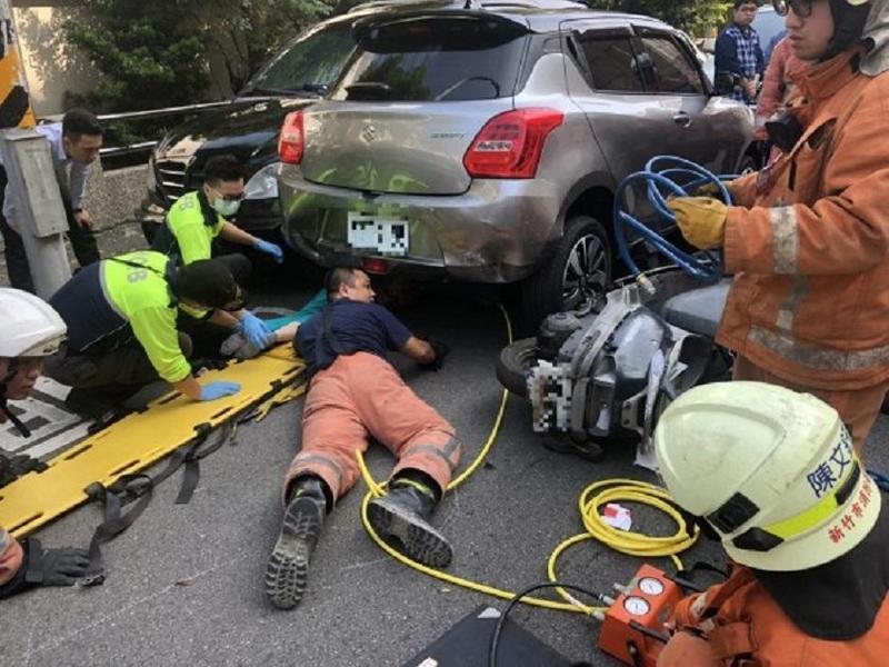 消防人員鑽到車底搶救老婦。(警方提供)
