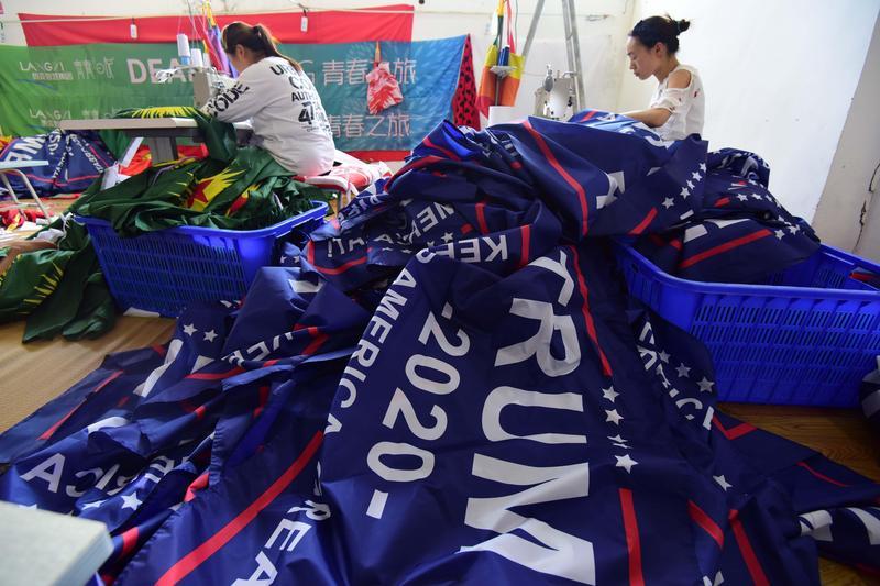 安徽省阜陽市,佳豪旗幟公司的工人在流水線上生產「川普2020」競選旗幟。以美國優先為口號的川普卻在中國製作競選旗幟,反映美中貿易的糾葛關係。(東方IC)