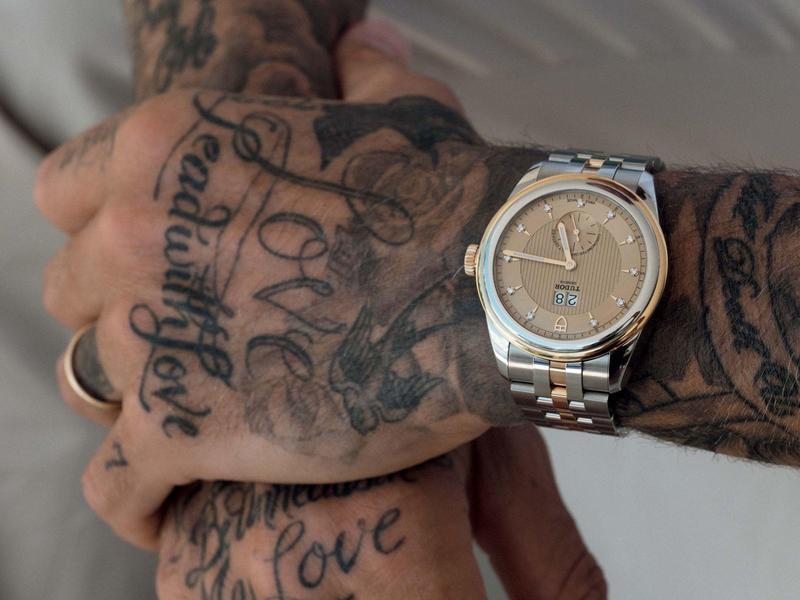 貝克漢滿是刺青的手臂,佩戴一款斯文的dress watch,呈現出更大的反差。反而有一種獨特的魅力。錶款是TUDOR Glamour Double Date大日曆半金錶款。售價未定。
