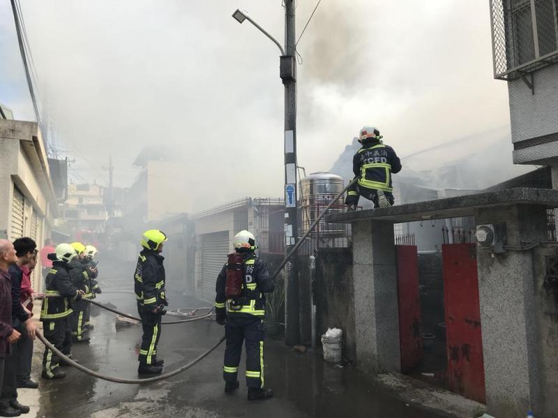 濃煙不斷竄出,消防人員強力噴水降溫,避免延燒四鄰。(消防局提供)