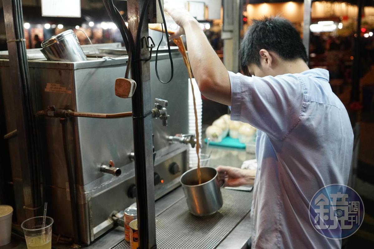 老闆在熱茶中加入煉乳,接著從高處倒入鐵杯,撞擊出茶香。