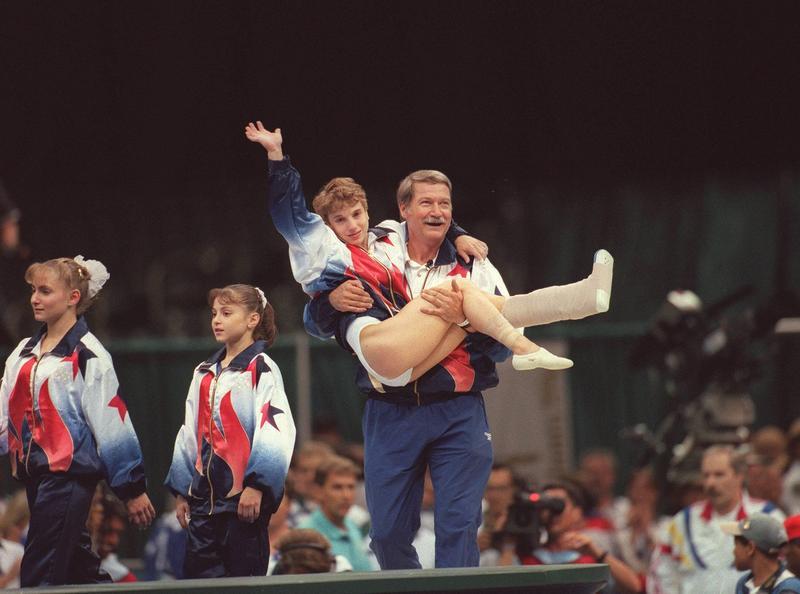 Kerri Strug在96年奧運會上帶傷完成比賽後,被教練抬起,揮手向觀眾致意。(東方IC)