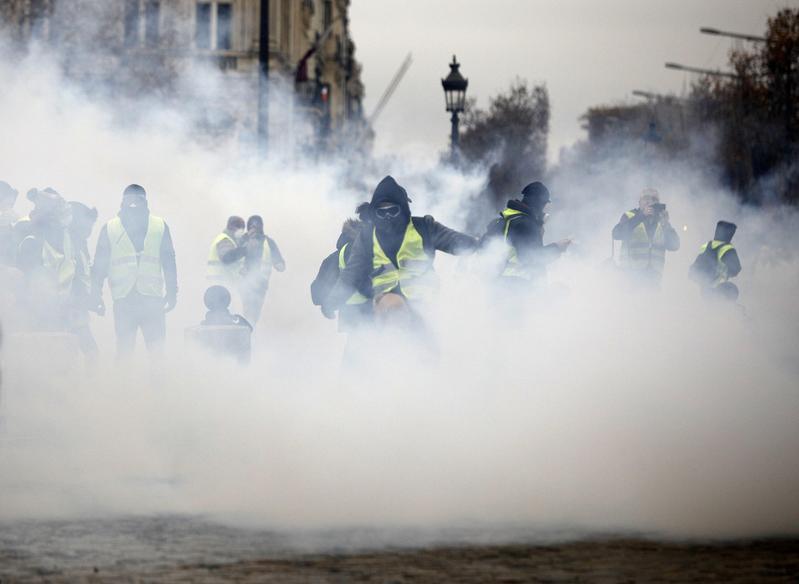 法國政府打算加徵燃油稅,身穿黃背心的示威者12月1日在巴黎香榭麗舍大道抗議,警方大陣仗以催淚瓦斯回應。(東方IC)