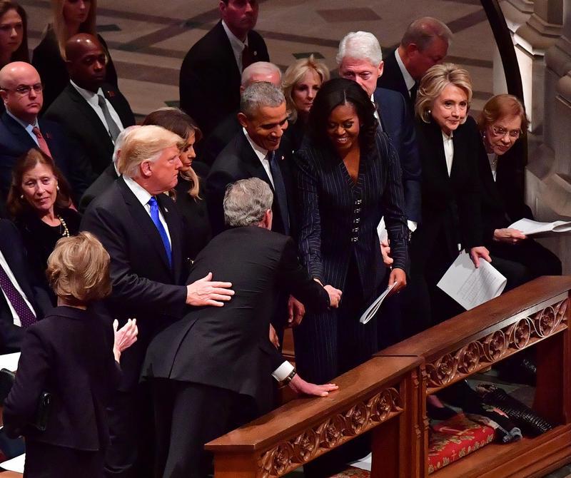 小布希與川普打招呼後,拿出糖果給前第一夫人蜜雪兒.歐巴馬的舉動,引發討論。(東方IC)