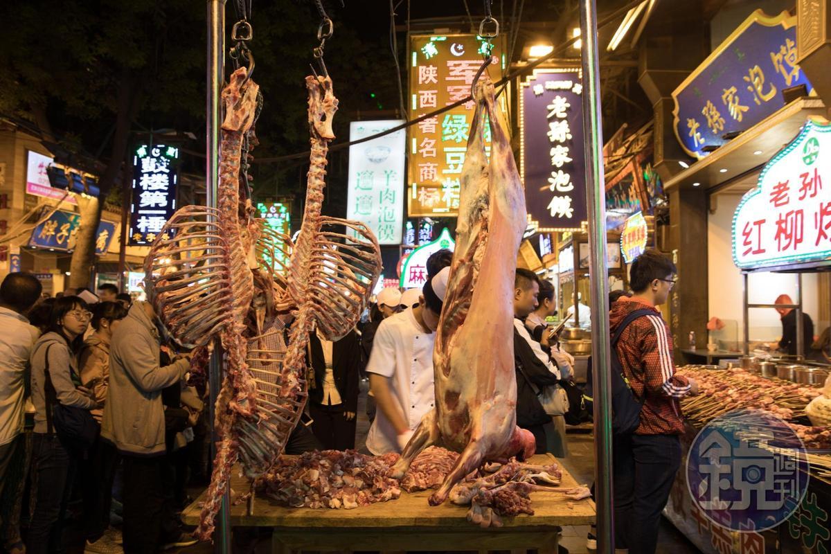 熱鬧的北院門街頭,「紅柳烤肉串」小攤旁大喇喇上演全羊肢解秀。