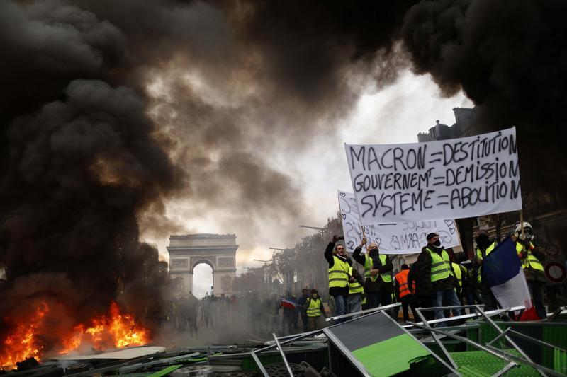 黃背心示威群眾燃燒路障,巴黎凱旋門前宛如烽煙戰場。(東方IC)