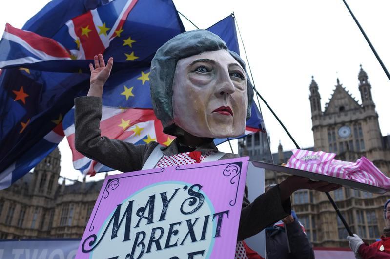 反對英國退歐示威者在議會廣場外面揮舞著歐盟和英國的旗幟,一名戴著Theresa May面具的示威者在廣場發放糖果。