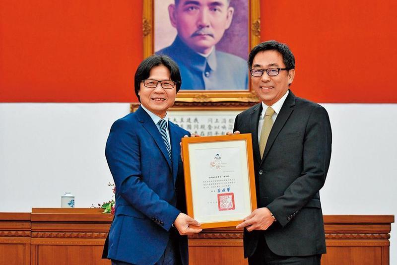 楊家駿(右)今年6月獲選為模範公務員,由當時的內政部長葉俊榮(左)頒獎表揚。(翻攝自內政部官網)