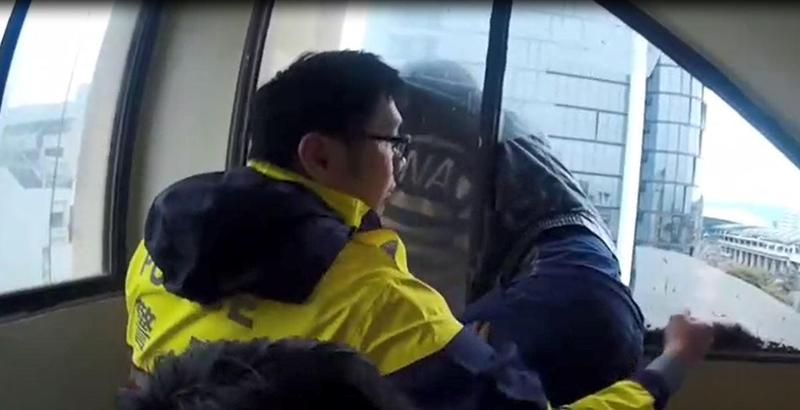 警方破窗、去除邊角玻璃,清出救人的空間,再將這對夫妻從窗緣險地來回來。(警方提供)
