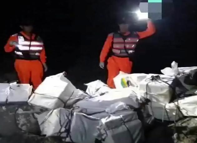 海巡人員逐一清點為數相當多的海洛英,用飼料袋包裝從海面上偷渡而來。(屏東地檢署提供)