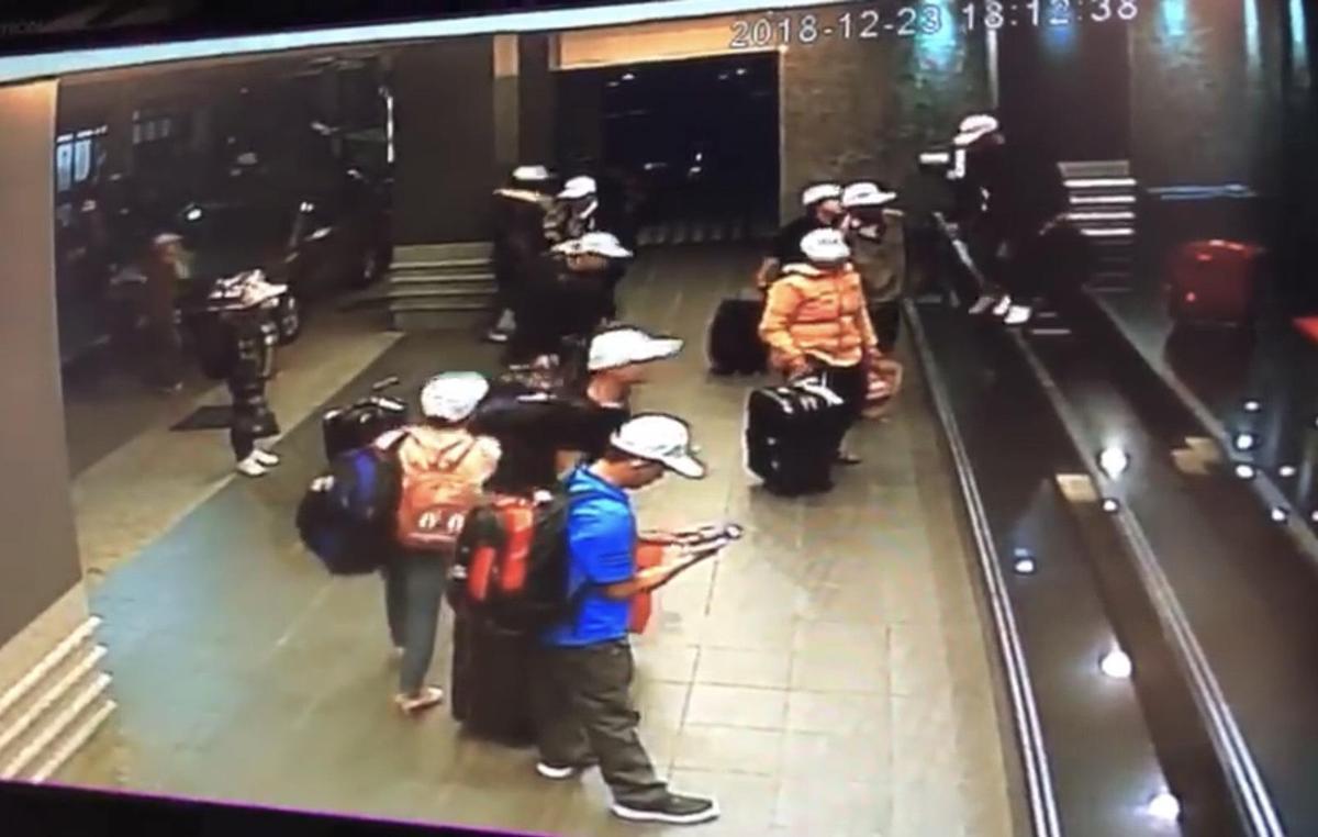 假觀光真偷渡畫面曝光,這團越南觀光客戴著白色帽子,下車並未急著入住飯店,疑似等著別人來接應。(翻攝畫面)