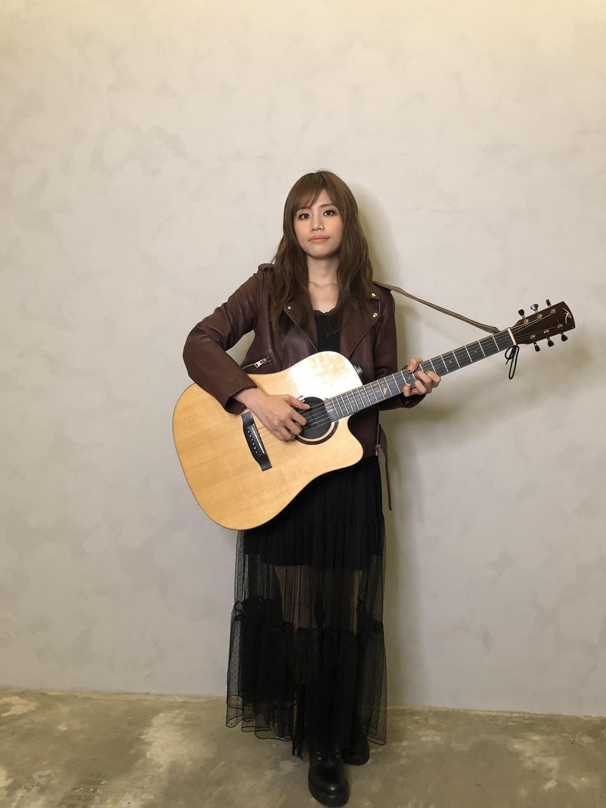 吳汶芳背著吉他開唱,展現溫暖音樂才華。(福茂唱片提供)