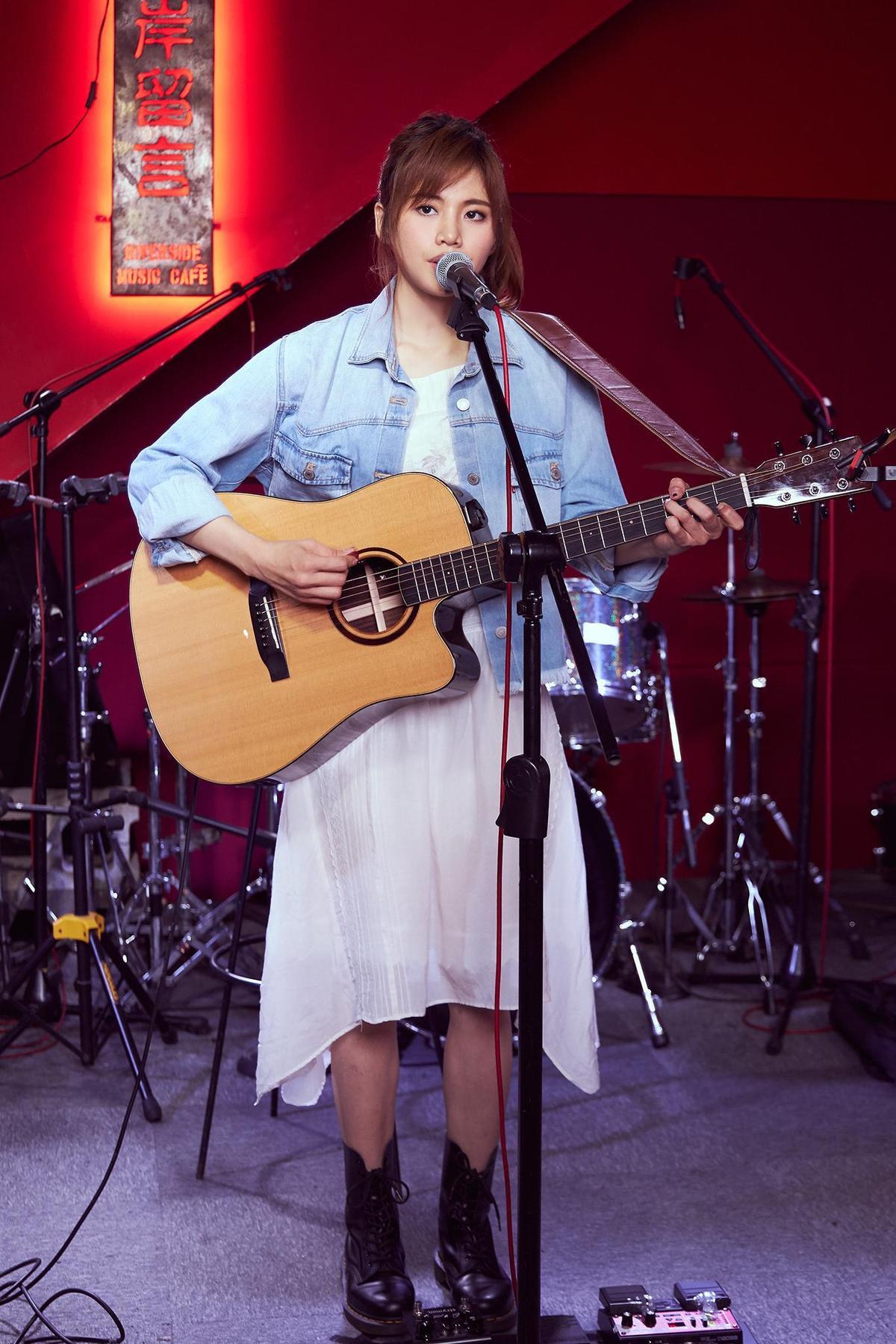 吳汶芳抱著吉他演唱自己的創作,一度哽咽。(福茂唱片提供)