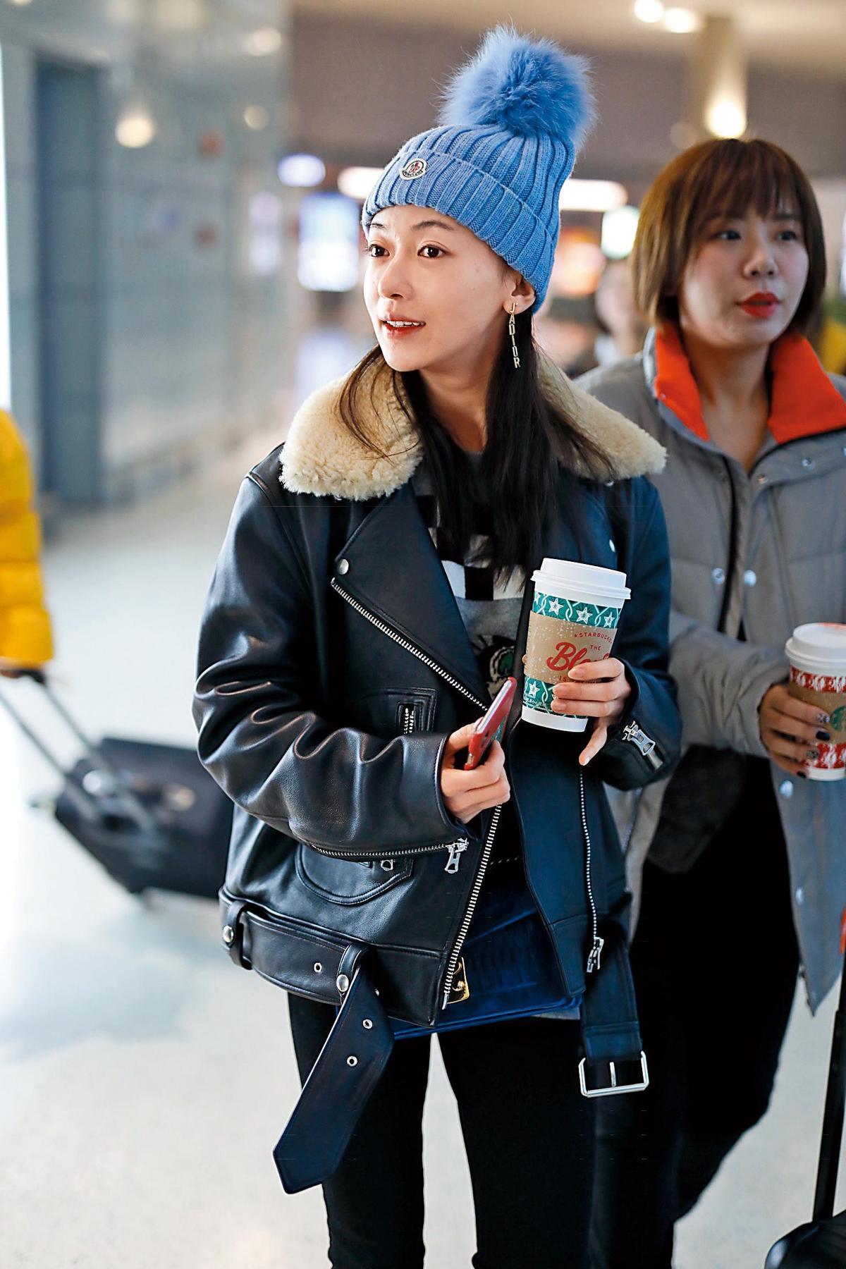 吳謹言 現身上海機場的吳謹言,機車騎士皮夾克穿在她嬌小的身體上有著帥氣感,藍色貂毛皮草的MONCLER毛帽在白皙的臉上更為凸顯,垂釣式的長耳環是神來之筆,讓人眼光都放在她的頸部以上。(東方IC)