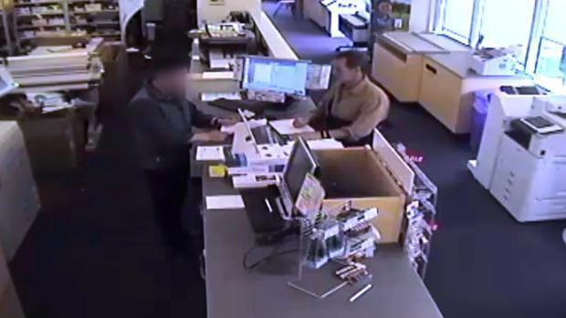 美國維吉尼亞州一家FedEx的監視器拍到馬洛里拿出一疊文件給店員,準備把這些資料掃描到一個可插入手機的SD卡中。(網路截圖)