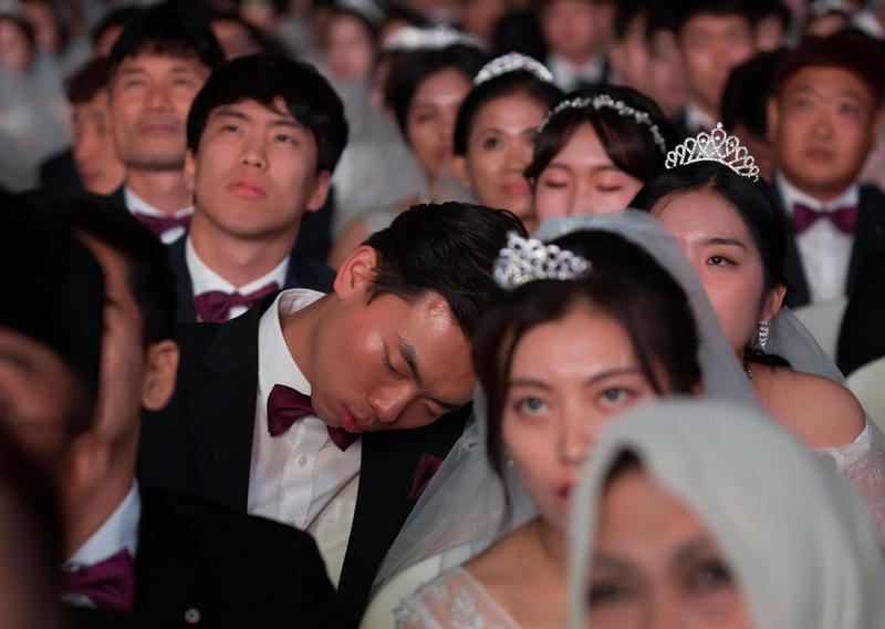 2018年8月27日,南韓加平郡清心和平世界中心的集團婚禮上,一名新郎在典禮中忍不住打起瞌睡。(東方IC)
