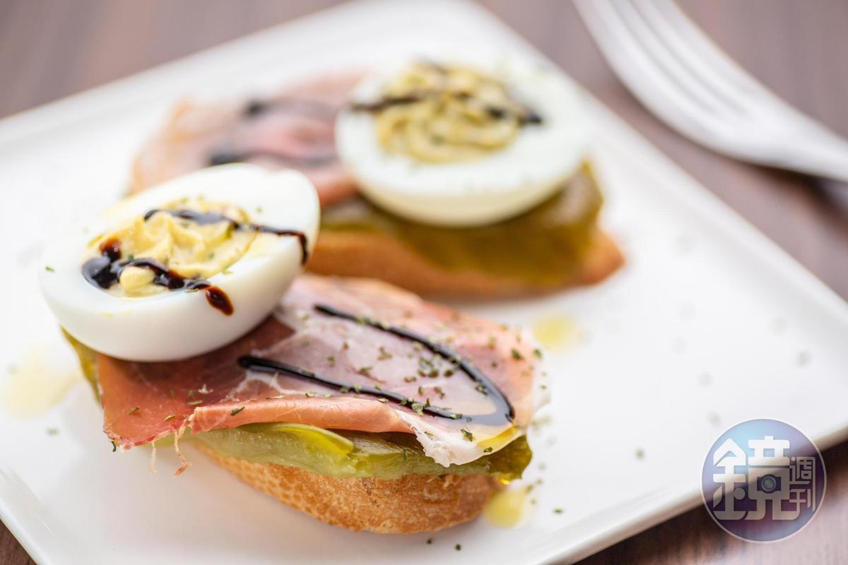 西班牙Tapas Bar常見的小點 Pintxo,以麵包襯底擺放伊比利火腿、烤青椒、魔鬼蛋、及自製蛋黃醬大蒜美奶滋,辣香有勁。