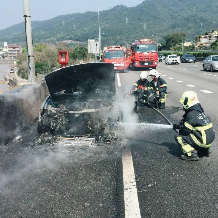 小客車被大火吞噬,消防隊員噴水灌救。(消防局提供)