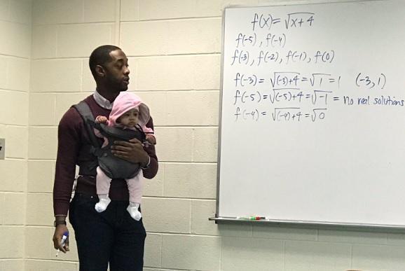 美國大學教授亞歷山大(Nathan Alexander)邊幫學生照顧女嬰,一邊寫下數學公式授課。(翻攝自推特)