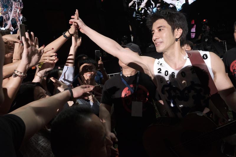 穿著背心的王力宏露出健壯的雙臂,面對粉絲「愛的小手」來者不拒,親民到最高點。(宏聲音樂提供)
