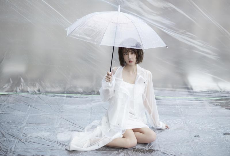 邵雨薇穿著白色透明雨衣洋裝,撐著雨傘趴在炙熱的柏油路上。(寬宏藝術Kham Music)