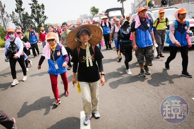 今年是方麗雯(戴斗笠者)第11年進香,身為年刊總編的她,一路上除了走,還幫我們調照片,為了白沙屯報導的正確性,反覆和記者確認細節。