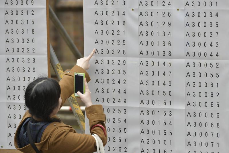日本正往免費大學教育的目標努力。圖為今年度東京大學入學考試時,準考生尋找自身號碼一景。(東方IC)