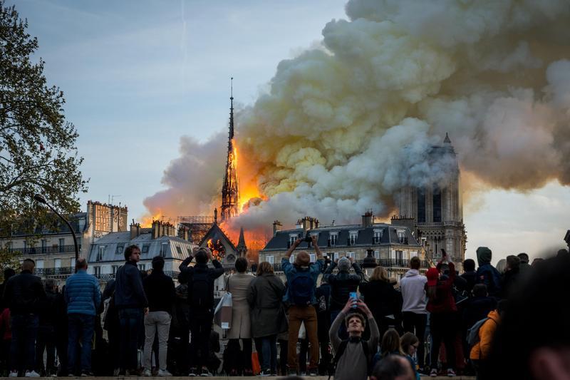 15日巴黎聖母院發生火災,塔尖在大火中坍塌,民眾看著燃燒的巴黎聖母院。(東方IC)