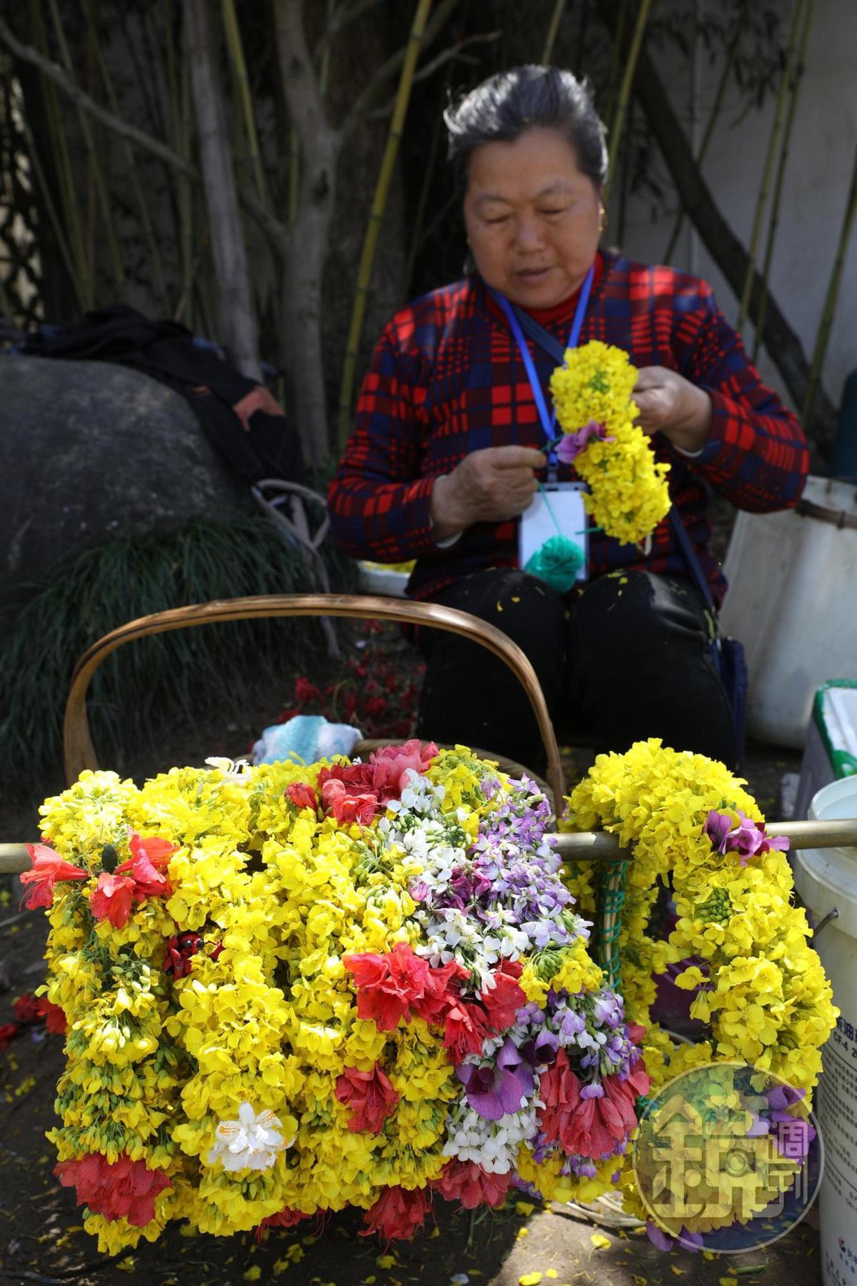 篁嶺景區外,許多婦人用油菜花綁成花圈出來兜售。