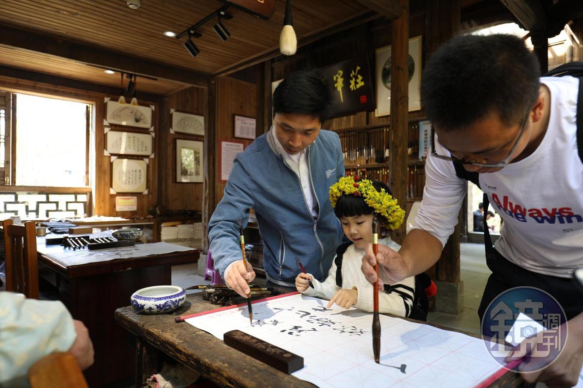 小女孩開心地試著用筆芯軟硬不同的毛筆寫字。