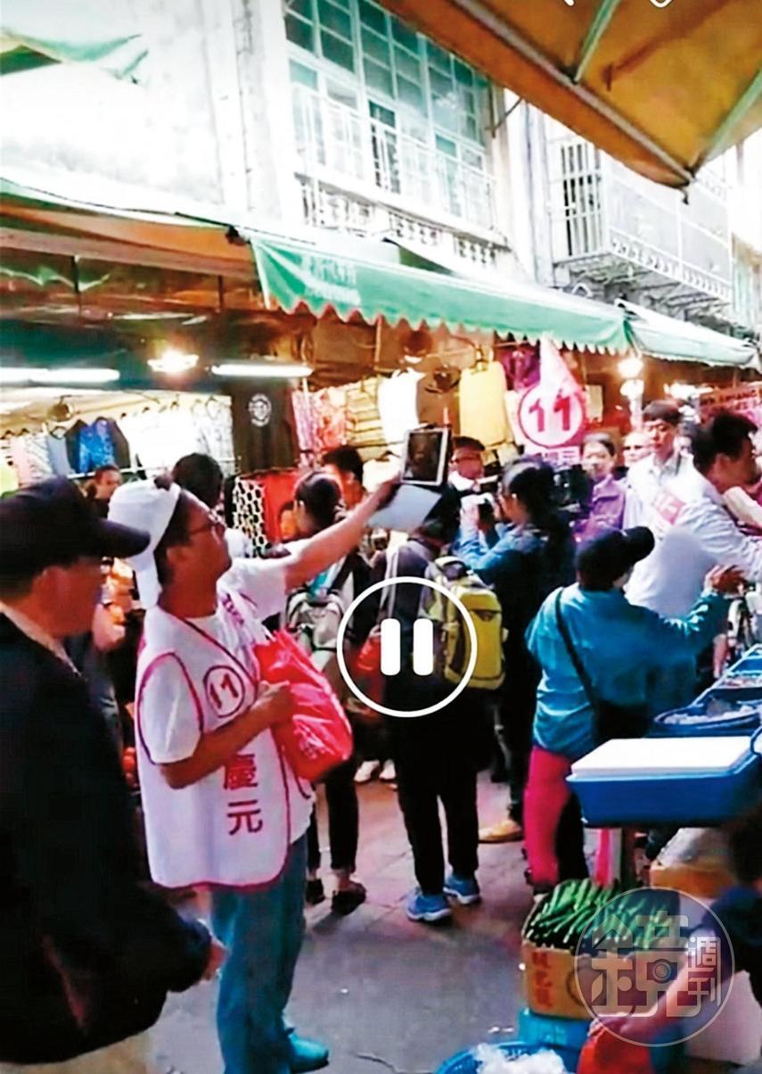安親班業者在臉書發現,聲稱公民記者的男子竟穿著李慶元的白色競選背心,還拿著同一台平板電腦,出現在李的造勢場合。(讀者提供)