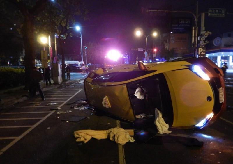 計程車側翻路中,零件散落一地。(警方提供)
