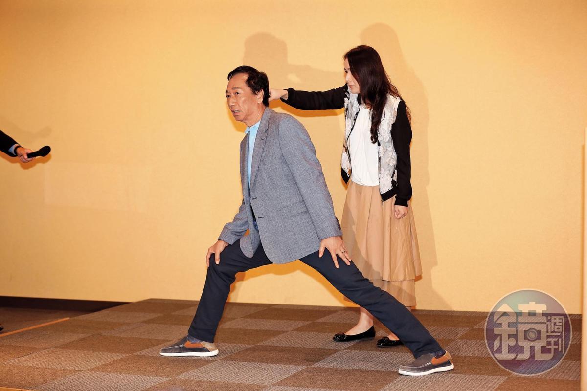 本月6日郭台銘(左)親自示範「雙腿論」,率領小編團隊的永齡基金會執行長劉宥彤(右)在旁替郭拿麥克風。