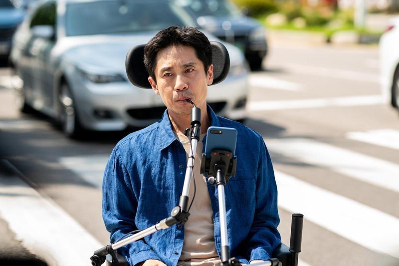 申河均在新片《完美搭檔》飾演肢體障礙者,以嘴巴操控輪椅。(采昌提供)