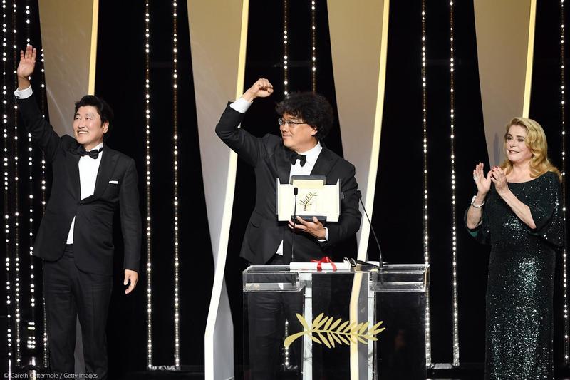 奉俊昊(中)以新作《寄生上流》斬獲坎城影展金棕櫚大獎,片中男主角宋康昊(左)也一同上台分享榮耀。(翻攝自坎城影展官方臉書)